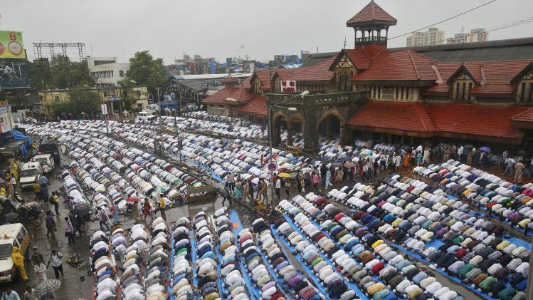 Muslims offer prayers during Eid al-Fitr outside a railway station in Mumbai