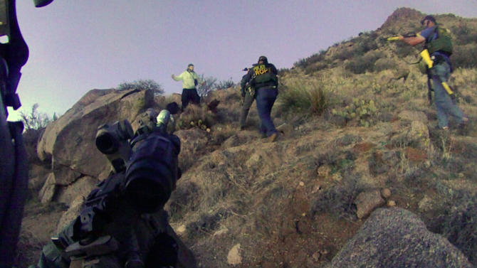 This March 16, 2014 photo of an Albuquerque Police Department lapel camera still, shows a standoff with an illegal camper in the Albuquerque foothills, before firing six shots at the man. Police say James Boyd, 38, refused to drop a knife and had threatened to kill officers. He later died at a nearby hospital but police have not said if he died from gunshot wounds. (AP Photo/Albuquerque Police Department)