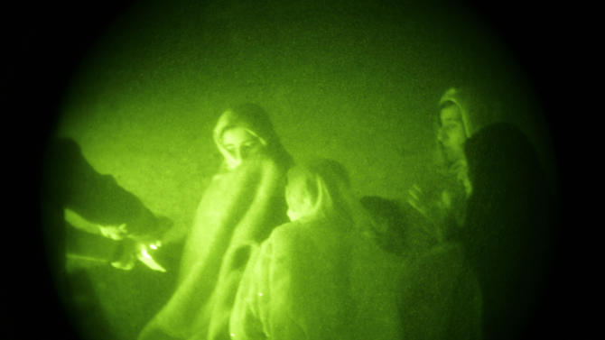 FILE - In this Wednesday, Oct. 28, 2009 file picture taken with a night vision scope, Afghan women and their children are asked about their male relatives as U.S. Special Operations forces and Afghan National Army soldiers search their home during a joint operation targeting insurgents operating in Afghanistan's Farah province. The U.S. Special Operations commander who directed the operation that killed Osama bin Laden defended the unpopular night raids on homes in Afghanistan that have provoked the fury of the country's president and held up a security agreement with the United States. Adm. William McRaven also backed a training program his troops run for village police forces _ an initiative that some fear could spawn militias and new violence.(AP Photo/Maya Alleruzzo, File)