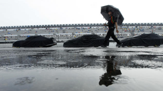 A crew member with the car of Mark Martin walks down pit road after rain halted NASCAR Sprint Cup Series auto race Sunday, Aug. 7, 2011, at Pocono Raceway in Long Pond, Pa. (AP Photo/Matt Slocum)
