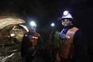 In this Sept. 25, 2012 photo, foreman Jorge Villanueva, left, and supervisor Omar Rosales, right, look toward the entrance of a tunnel drilled under the Chuquicamata copper mine in the Atacama desert in northern Chile. Experts say that by 2019 the Chuquicamata copper mine will be unprofitable, so state-owned mining company Codelco is trying to head off closure by converting the open pit into the world's largest underground mine. Codelco believes the mine still has much more to give, with reserves equal to about 60 percent of all the copper exploited in the mine's history still buried deep beneath the crater. (AP Photo/Jorge Saenz)