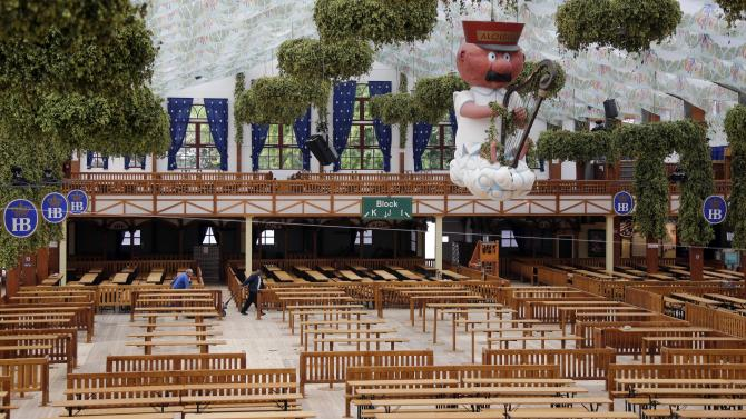 Employees of the 'Hofbraeuhaus' beer tent walk past empty tables and benches during preparations for the 181th Oktoberfest beer festival in Munich, southern Germany, Wednesday, Sept 17, 2014. One of the world's biggest beer festival will be held from Sept. 22 to Oct. 5, 2014. (AP Photo/Matthias Schrader)