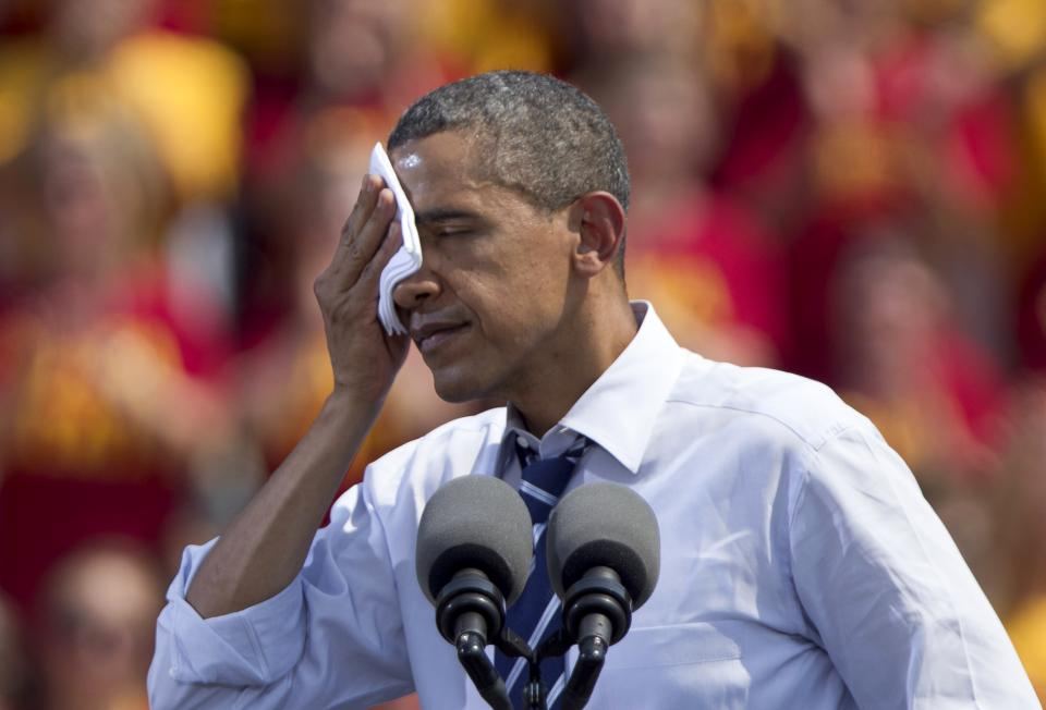 President Barack Obama wipes sweat off his face as he speaks during a campaign stop in Ames, Iowa, Tuesday, Aug. 28, 2012. The president's event in Ames, home of Iowa State University, is part of a tour through college towns. (AP Photo/Nati Harnik)