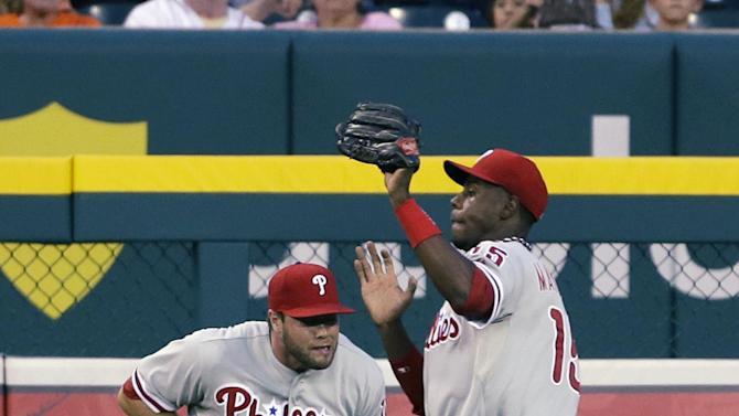 Philadelphia Phillies outfielder John Mayberry Jr., right, catches a fly ball by Detroit Tigers' Hernan Perez and avoids Darin Ruf during the sixth inning of a baseball game in Detroit, Friday, July 26, 2013. (AP Photo/Carlos Osorio)