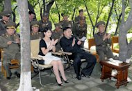 North Korean leader Kim Jong-Un (C) accompanied by his wife Ri Sol-Ju (centre L) visit a Korean People's Army Unit. North Korea's young first lady has been pictured sporting what appears to be a Christian Dior handbag, in stark contrast to widespread shortages elsewhere in the impoverished nation