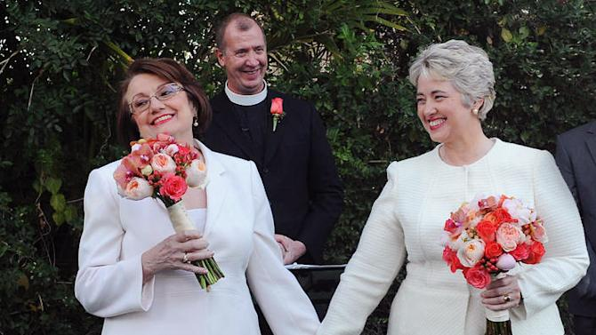 In this photo provided by the Houston mayor's office, Houston Mayor Annise Parker, right and her long-time partner, First Lady Kathy Hubbard, celebrate at their wedding Thursday, Jan 16, 1014 in Palm Springs, Calif. The ceremony was performed by the Rev. Paul Fromberg, rear, rector of St. Gregory of Nyssa Episcopal Church in San Francisco. (AP Photo/Houston Office of The Mayor, Richard Hartog)