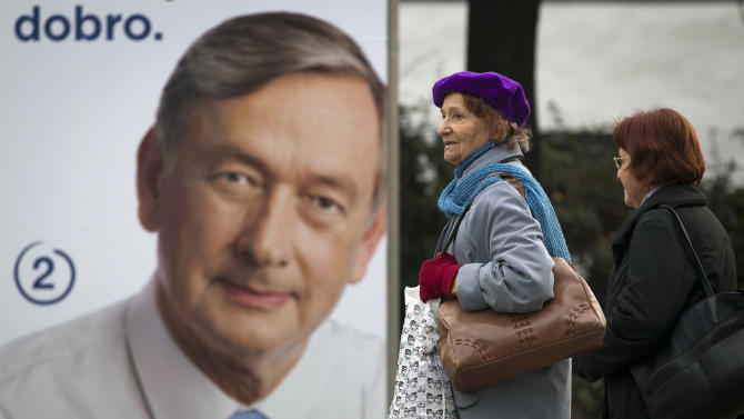 Residents walk past an electoral poster of Danilo Turk in Ljubljana, Slovenia, Saturday, Nov. 10, 2012. Three candidates are vying for the presidency this weekend in crisis-stricken Euro zone member, Slovenia, where deep political divisions have threatened efforts at reforms needed to avoid possible bailout. Incumbent president Danilo Turk is leading the polls. (AP Photo/Darko Bandic)