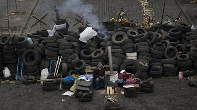 An anti-Yanukovych protester warms himself next to a fire as he guards a barricade in a street heading to Kiev's Independence Square, the epicenter of the country's current unrest, Ukraine, Friday, Feb. 28, 2014. Fugitive Ukrainian president Viktor Yanukovych on Friday pledged to fight for his country's future, in his first public appearance since disappearing from Ukraine. (AP Photo/Emilio Morenatti)