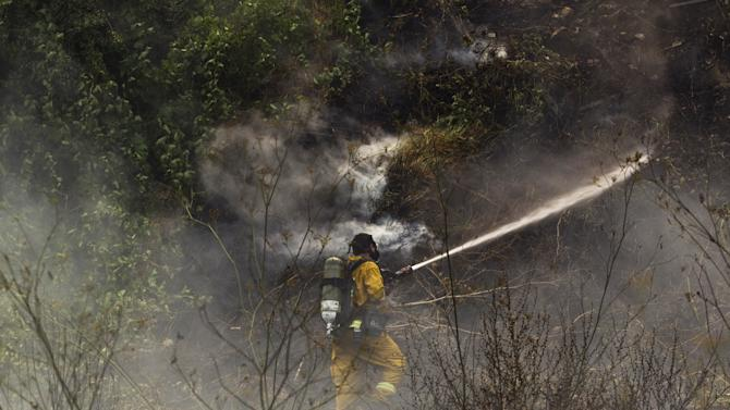 A firefighter sprays water as he works to contain a forest fire in Even Sapir