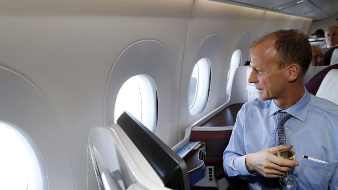 Tom Enders, Chief Executive Officer of Airbus Group drinks champagne during the flight of the first delivery of the new Airbus passenger jet to Qatar Airways in Toulouse