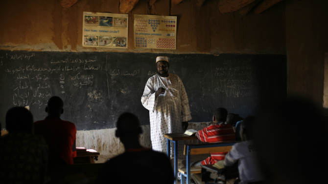 In this photo taken Monday, Feb. 18, 2013, Mohamed Salia teaches in his Madrassa in Gao, northern Mali. Nearly a month after the al-Qaida-linked militants were driven out of Gao and into the surrounding villages, students are now returning to the city's Quranic schools. Many classrooms, though, are still half full, as tens of thousands of people fled the fighting and strict Islamic rule imposed by the extremists. However, other pupils left Gao not with their families but with the Islamic fighters when they retreated, say human rights activists and local officials. (AP Photo/Jerome Delay)
