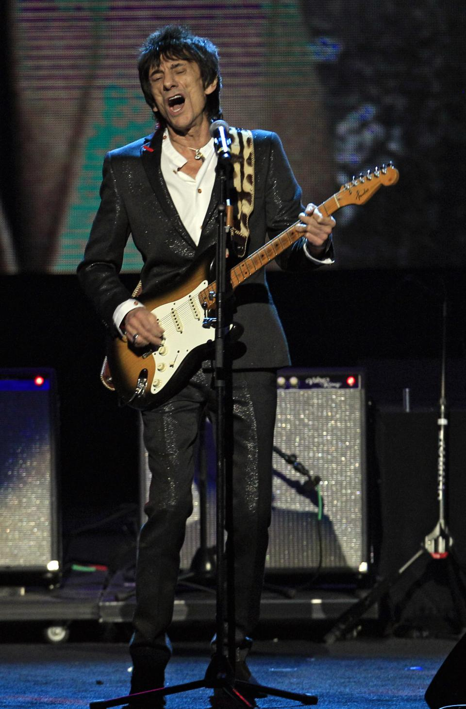 Rolling Stones guitarist Ron Wood performs after being inducted into the Rock and Roll Hall of Fame as a member of Faces Saturday, April 14, 2012, in Cleveland. (AP Photo/Tony Dejak)