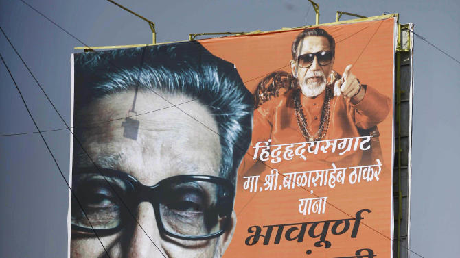 """Indian mourners climb on a billboard of Hindu hardline Shiv Sena party leader Bal Thackeray during his funeral in Mumbai, India, Sunday, Nov. 18, 2012. Thackeray, the extremist leader linked to waves of mob violence against Muslims and migrant workers in India, died Saturday after an illness of several weeks. He was 86. The billboard reads, """"Emotional Homage."""" (AP Photo/Rafiq Maqbool)"""