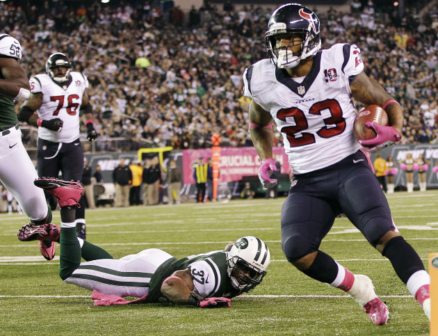 Houston Texans running back Arian Foster (23) rushes for a touchdown as New York Jets strong safety Yeremiah Bell (37) falls down on the play during the first half of an NFL football game, Monday, Oct