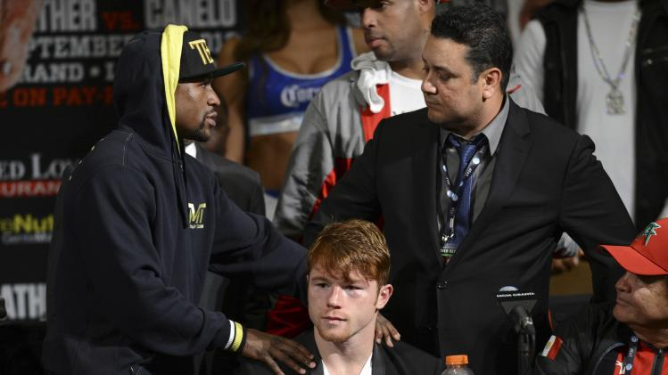 Mayweather of the U.S. talks with Alvarez of Mexico and his camp during a post-fight news conference in Las Vegas