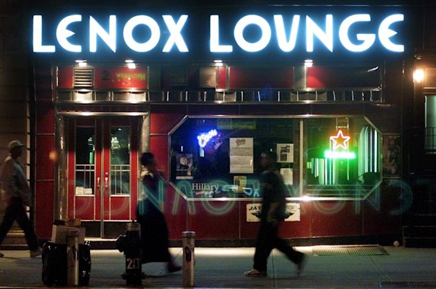 FILE - In this Oct. 19, 2000 file photo, pedestrians pass by the Lenox Lounge in the Harlem neighborhood of New York. Longtime owner Alvin Reed says that the Harlem cabaret with a supercool, Art Deco style that made it a favorite of jazz greats like Billie Holiday, Miles Davis and John Coltrane, is closing its doors on New Year's Eve. (AP Photo/Suzanne Plunkett, File)