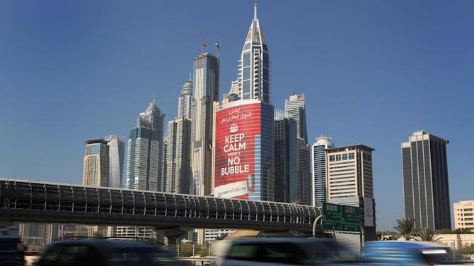 """In this Wednesday Nov. 13, 2013 photo, vehicles pass by a tower with a sign that reads, """"Keep Calm, No Bubble,"""" at the Marina district in Dubai, United Arab Emirates. The logo for Dubai's bid to host the Expo 2020 reflects a push by the city's leaders to avert another financial crisis like the one that brought the city to its knees in 2008. Dubai saw property values slashed by more than half and the city's government needed a $10 billion bailout from oil-rich neighbor Abu Dhabi in 2009. (AP Photo/Kamran Jebreili)"""