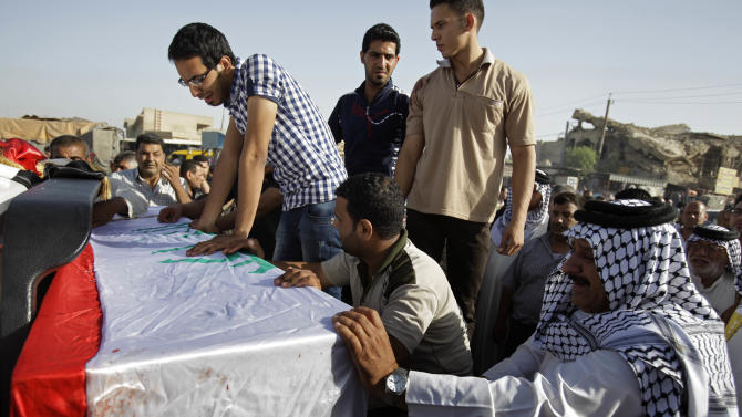 Relatives react over the coffin of Ali al-Lami, the director for the Accountability and Justice Committee in Baghdad, Iraq, Friday, May 27, 2011. Scores of people have taken part in the funeral procession for the assassinated Iraqi Shiite official who headed a committee tasked with rooting out those with ties to Saddam Hussein.  The casket of Ali al-Lami, wrapped in the Iraqi flag, was carried on Friday morning by his weeping relatives and friends from his home in Baghdad's eastern district of Sadr City. He was to be buried in the holy Shiite city of Najaf in the south.  (AP Photo/Karim Kadim)