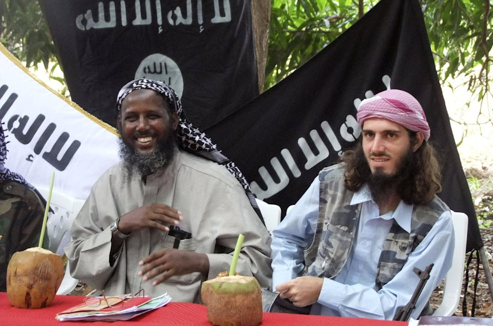 "FILE - In this Wednesday, May 11, 2011 file photo, American-born Islamist militant Omar Hammami, right, and deputy leader of al-Shabab Sheik Mukhtar Abu Mansur Robow, left, sit under a banner which reads ""Allah is Great"" during a news conference of the militant group at a farm in southern Mogadishu's Afgoye district in Somalia. Hammami, a jihadi from Alabama whose nom de guerre is Abu Mansoor Al-Amriki, or ""the American,"" and ascended the ranks of Somalia's al-Qaida-linked militant group al-Shabab high enough to attract a $5 million U.S. government bounty, was killed Thursday, Sept. 12, 2013 in an ambush ordered by the militant group's leader, militants said. (AP Photo/Farah Abdi Warsameh, File)"