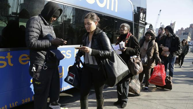 FILE- In this Nov. 25, 2015 file photo, travelers line up to board a bus in New York. AAA estimated that 42 million people traveled somewhere for Thanksgiving. Tens of millions of Americans returning home after the long Thanksgiving holiday weekend Sunday have cooperative weather and mostly efficient airport operations to thank for smooth traveling conditions. (AP Photo/Mark Lennihan, File)