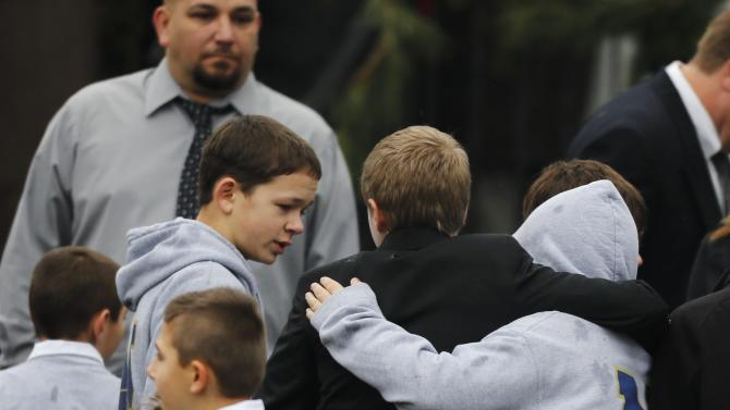 Studens embrace while wearing Newtown school shirts outside the funeral for six-year-old student shooting victim Jack Pinto in Newtown, Conn., Monday, Dec. 17, 2012. A gunman opened fire at Sandy Hook Elementary School in the town on Friday, killing 26 people, including 20 children before killing himself. (AP Photo/Charles Krupa)