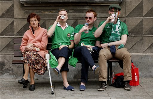 Irish fans drink beer while sitting on a bench with a Polish woman ahead of the Euro 2012 soccer championship Group C match between Ireland and Spain in Gdansk, Poland , Thursday, June 14, 2012. (AP P