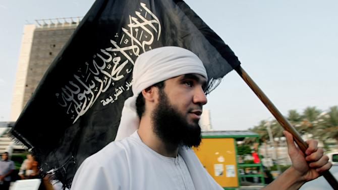 "FILE -- In this Friday, Sept. 14, 2012 file photo, a Libyan follower of Ansar al-Shariah Brigades chants as he carries the Brigades flag, with Arabic writing that reads, ""There is no God but Allah and Muhammad is his messenger, Ansar al-Shariah,"" during a protest in front of the Tibesti Hotel, in Benghazi, Libya. Libya's upheaval the past two years helped lead to the ongoing conflict in Mali, and now Mali's war threatens to wash back and further hike Libya's instability. There is a growing fear that post-Moammar Gadhafi Libya is becoming an incubator of turmoil, with an overflow of weapons and Islamic jihadi militants operating freely, ready for battlefields at home or abroad. (AP Photo/Mohammad Hannon, File)"