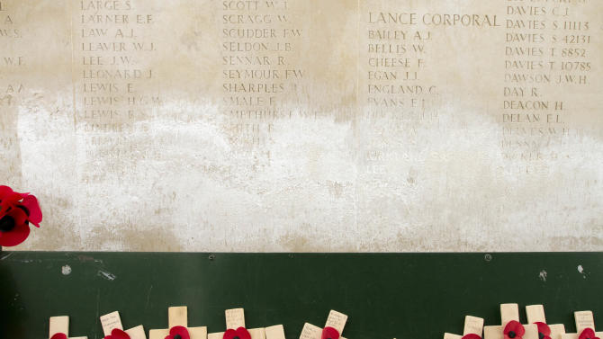 Wooden crosses with paper poppies are seen in front of a damaged  stone wall with names of missing WWI solders on it at the Menin Gate in Ypres, Belgium on Monday, April 15, 2013. Commonwealth cemeteries and monuments around the world are currently being renovated in preparation for centenary events which begin in 2014. At the Menin Gate, work has already begun on replacing damaged stone panels with newly engraved panels. (AP Photo/Virginia Mayo)