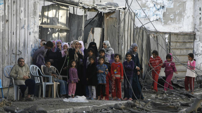 Palestinians stand near the rubble of the building of Attia Abu Inkara, a Hamas militant leader, following an Israeli air strike in Rafah refugee camp in southern Gaza Strip, Sunday, Nov. 18, 2012. An Israeli envoy held talks with Egyptian officials Sunday on a ceasefire in his country's offensive on Gaza as Israel widened the range of its targets, striking more than a dozen homes of Hamas militants and two media officials. (AP Photo/Eyad Baba)