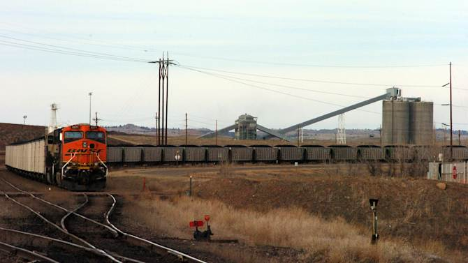 """In this Jan. 16, 2013 photo, a coal train idles in front of the Decker Coal Mine near the Wyoming border in  Decker, Mont. The mine once produced 10 million tons of coal a year """"like clockwork,"""" but is now down to less than a third of that volume as contracts dry up amid slackening demand for the fuel. (AP Photo/Matthew Brown)"""