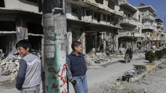 """Syrian boys, stand in  a destroyed street which was damaged by the shelling of the Syrian forces, at Maarat al-Nuaman town, in Idlib province, Syria, Tuesday Feb. 26, 2013. Syrian rebels battled government troops near a landmark 12th century mosque in the northern city of Aleppo on Tuesday, while fierce clashes raged around a police academy west of the city, activists said. the Arabic words read:""""Freedom for ever"""".  (AP Photo/Hussein Malla)"""