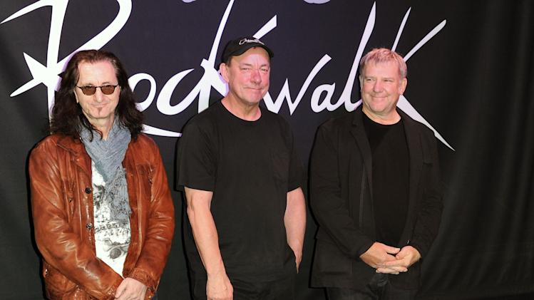 "FILE - This Nov. 20, 2012 file photo shows members of the band Rush, from left, Geddy Lee, Neil Peart, and Alex Lifeson at the RockWalk induction of Rush at Guitar Center in Los Angeles. The eclectic group of rockers Rush and Heart, rappers Public Enemy, songwriter Randy Newman, ""Queen of Disco"" Donna Summer and bluesman Albert King will be inducted into the Rock and Roll Hall of Fame next April in Los Angeles. The inductees were announced Tuesday by 2012 inductee Flea of The Red Hot Chili Peppers at a news conference in Los Angeles. (Photo by Richard Shotwell/Invision/AP, file)"
