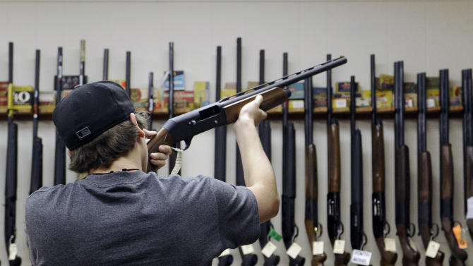 In this photo taken Wednesday, Dec. 19, 2012, a customer checks out a shotgun at Burdett & Son Outdoor Adventure Shop in College Station, Texas. More civilians are armed in the U.S. than anywhere else in the world, with Yemen coming in a distant second, according to the Small Arms Survey in Geneva. (AP Photo/Pat Sullivan)