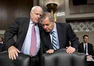 Senate Armed Services Committee members, Sen. John McCain, R-Ariz., left, and Sen. Lindsey Graham, R-S.C. confer on Capitol Hill in Washington, Thursday, Feb. 14, 2013, at the start of the committee's hearing on the appointments of military leaders. The two Republicans have been vocal in their opposition to the nomination of Chuck Hagel to be the next secretary of defense. While Democrats hold a 55-45 edge in the Senate and have the numbers to confirm Hagel on a majority vote, they need the support of five Republicans to clear the way for an up-or-down vote on him. (AP Photo/J. Scott Applewhite)