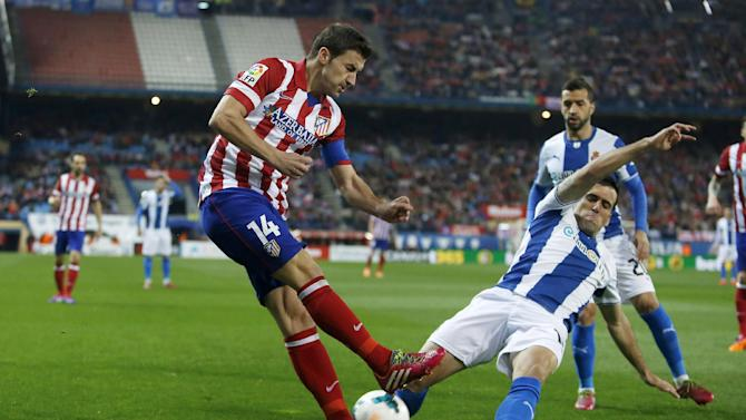 Atletico's Gabi, left, vies for the ball with Espanyol's Juan Fuentes, right, during a Spanish La Liga soccer match between Atletico Madrid and Espanyol at the Vicente Calderon stadium in Madrid, Spain, Saturday, March 15, 2014