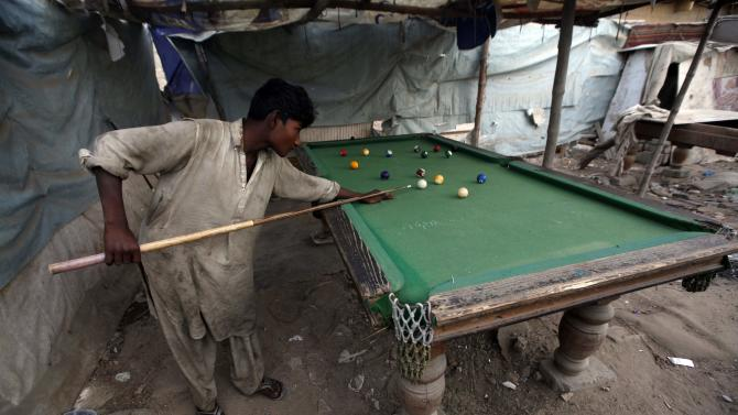 A boy plays snooker at a slum on the outskirts of Karachi