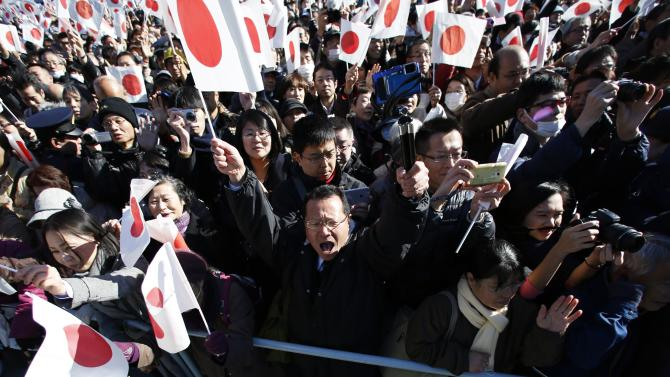A man raises his fists as he shouts 'banzai' as well-wishers wave Japanese national flags to celebrate Japan's Emperor Akihito's 81st birthday at the Imperial Palace in Tokyo