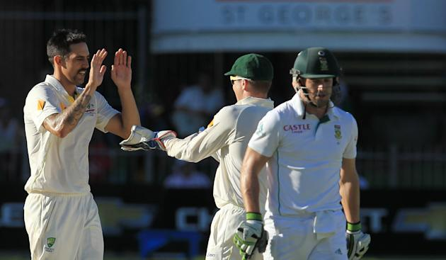 Australia's bowler Mitchell Johnson, left, celebrates with teammate Brad Haddin, center, after dismissing South Africa's batsman AB de Villiers, right, for 29 runs on the third day of their 2n
