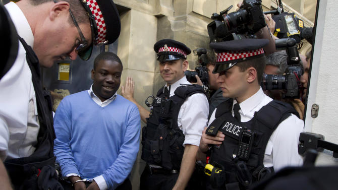 FILE - In this Sept. 16, 2011 file photo, former UBS trader Kweku Adoboli, second from left, walks to be taken away in a security van flanked by police officers after appearing at the City of London Magistrates Court in London. Britain's financial regulator said Monday, Nov. 26, 2012 that it has fined Swiss bank UBS AG for failings which allowed rogue trader Kweku Adoboli to lose $2.3 billion. (AP Photo/Matt Dunham, File)