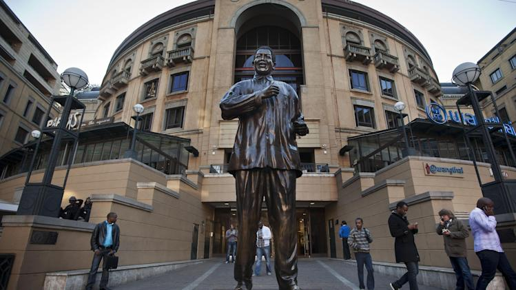 Visitors walk past a statue of Nelson Mandela in Nelson Mandela Square at the Sandton City shopping centre in Johannesburg, South Africa Tuesday, June 11, 2013. Doctors are doing all they can to improve Nelson Mandela's health as the 94-year-old icon spent a fourth day in the hospital for a recurring lung infection, South Africa's president said Tuesday, as two of Mandela's daughters visited their father. (AP Photo/Ben Curtis)