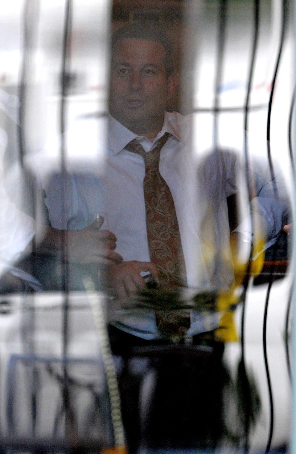 Casey Anthony lead defense attorney Jose Baez, center, is seen through a window participating in a celebration with other members of his defense team and staff at a restaurant across the street from the Orange County Courthouse after the not-guilty verdict was announced in Orlando, Fla., Tuesday, July 5, 2011. (AP Photo/Phelan M. Ebenhack)