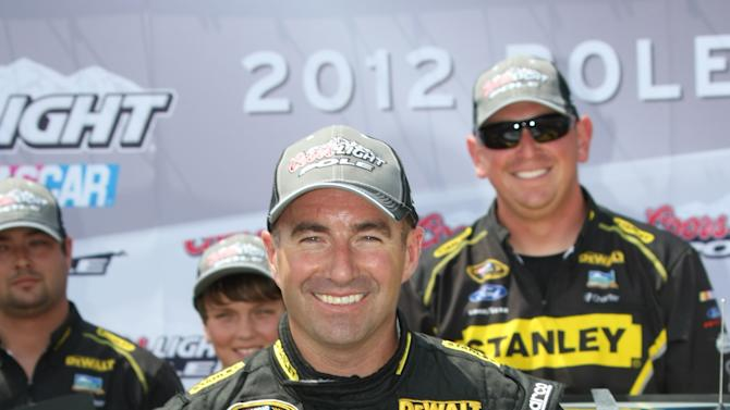 Driver Marcos Ambrose, of Australia, poses with the pole sitter flag after qualifying for Sunday's NASCAR Sprint Cup Series Quicken Loans 400 auto race at Michigan International Speedway in Brooklyn, Mich., Saturday, June 16, 2012. (AP Photo/Bob Brodbeck)