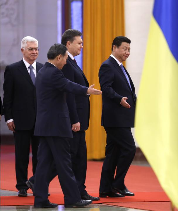 China's President Xi Jinping shows the way to his Ukrainian counterpart Viktor Yanukovich in Beijing