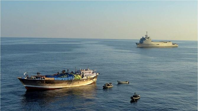 Picture released by the EU NAVFOR on January 20, 2014 shows crew of the French EU Naval Force ship FS Siroco (background) during an operation off Oman to release the crew of a dhow (L) suspected to have been used as pirate mother-ship