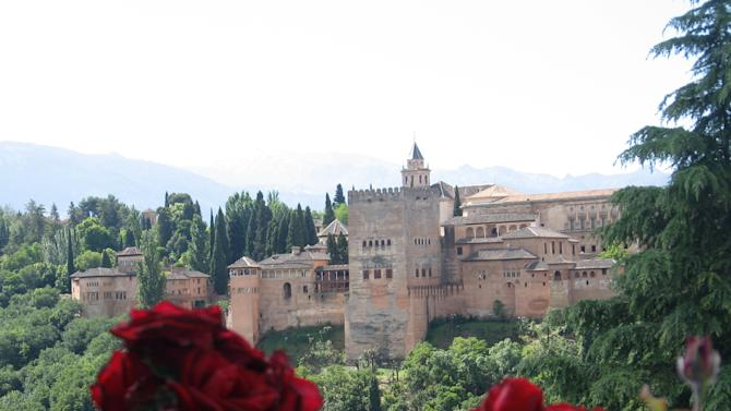 This May 29, 2013 photo shows roses in the garden of a mosque in the Albaicin neighborhood in Granada, in Andalusia, Spain, framing the Alhambra, the city's medieval Islamic palace complex. Andalusia offers a fusion of Christian and Islamic cultures, found in architectural masterpieces and in everyday life. (AP Photo/Giovanna Dell'Orto)