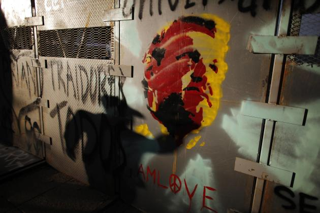 A demonstrator casts his shadow on a fence with a graffiti of leftist leader Andres Manuel Lopez Obrador, who is recovering from a heart attack at a hospital, during a protest against an energy reform