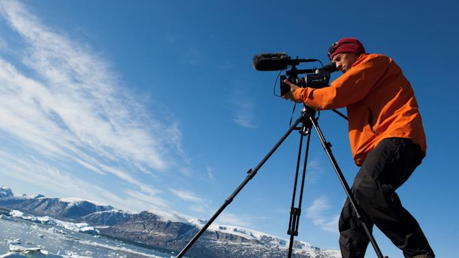"""This 2007 photo released by Extreme Ice Survey shows """"Chasing Ice"""" director Jeffery Orlowski shooting in Uummannaq, Greenland. The film, about climate change, follows National Geographic photographer James Balog across the Arctic as he deploys revolutionary time-lapse cameras designed to capture a multi-year record of the world's changing glaciers. (AP Photo/Extreme Ice Survey, James Balog)"""