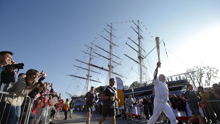 Sir Robin Knox Johnson, 73, right, runs with the Olympic torch past the Cutty Sark ship, Saturday, July 21, 2012, in Greenwich, London. The Olympic Torch arrived in London after it was carried around England in a relay of torchbearers to make its way to the London 2012 Olympic Games opening ceremony on July 27, 2012. (AP Photo/Jae C. Hong)