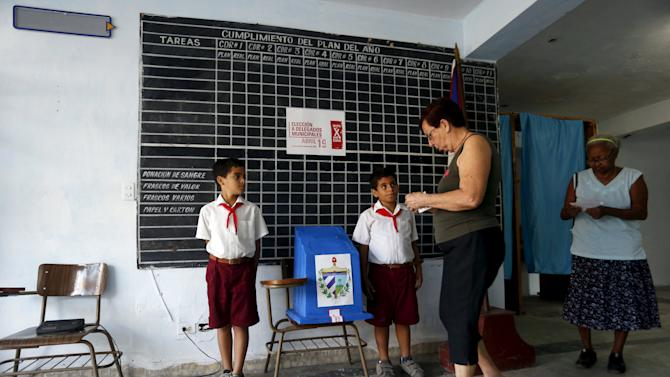 Women walk to the ballot box to cast their votes at a polling station set up at a central office of the Committees for the Defence of the Revolution (CDR) for this district in Havana