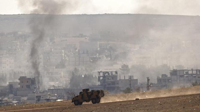A Turkish military vehicle drives on a hillside backdropped by destroyed buildings in the town of Kobani following airstrikes by the US led coalition, seen from the outskirts of Suruc, near the Turkey-Syria border, Wednesday, Oct. 29, 2014. Kobani, also known as Ayn Arab, and its surrounding areas, has been under assault by extremists of the Islamic State group since mid-September and is being defended by Kurdish fighters. (AP Photo/Vadim Ghirda)